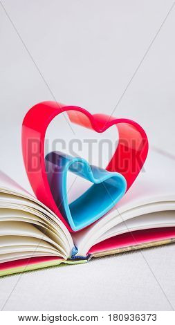 Red and blue hearts over diary book on white table, vertical orientation.