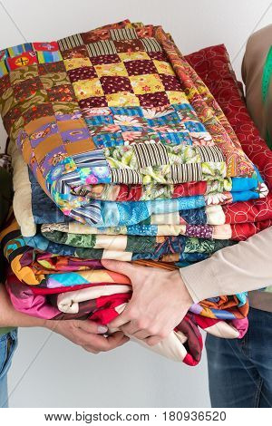 quilting and needlework at the workshop - close up on tailor hands holding the finished product made of pieces colored patchwork fabrics. Sewing and hobby concept.