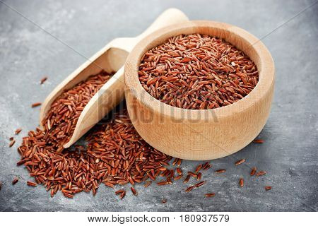 Red rice in wooden bowl on table