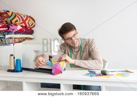 quilting at the workshop of tailor male - smiling tailor with glasses and measuring tape on the neck works on the sewing machine with brightly colored patchwork and looking to the side. Sewing concept