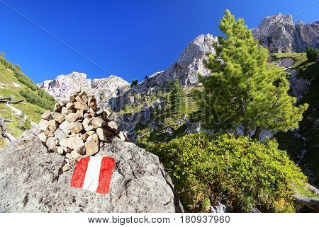 Tourist sign and stone pyramid in Dolomites alps mountains Italy