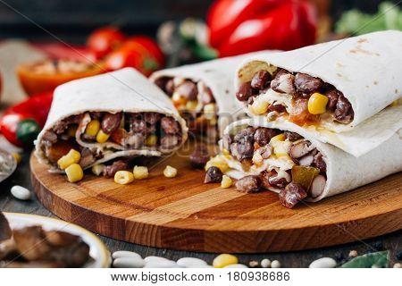 Nice Vegetarian Burrito Over Black Table On Wooden Board.
