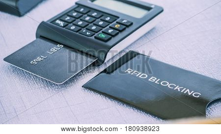 Black colour protection sleeve for secure credit card from fraud in front and TAN generator with credit card in it on middle ground poster