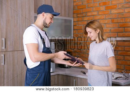 Woman signing receipt for plumber service at home poster