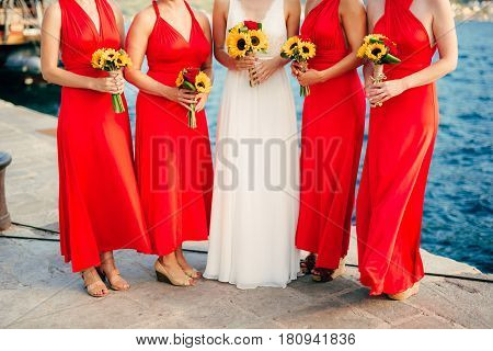 Bridesmaids in red dresses, in hands bouquets of sunflowers. Wedding on the sea, in Montenegro.