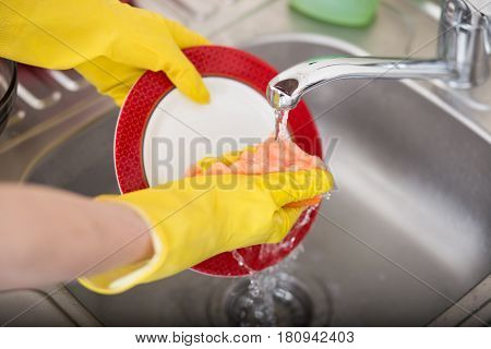 Cleaning dishware kitchen sink sponge washing dish. Close up of female hands in yellow protective rubber gloves washing
