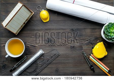 profession concept with architect desk and constructor tools and tea on wooden background top view mockup