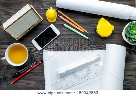 profession concept with architect desk and constructor tools and tea on wooden background top view