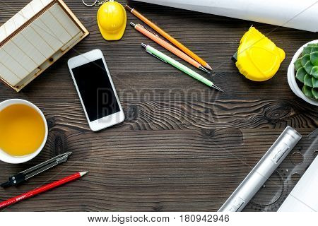 profession concept with architect desk and constructor tools and phone on wooden background top view mock-up
