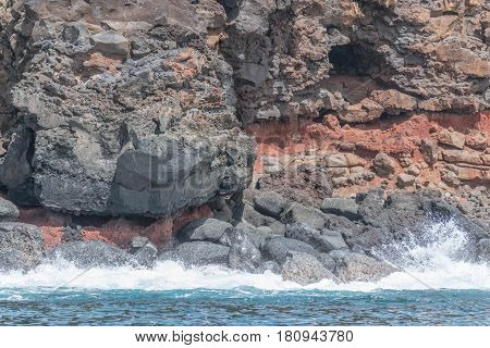 Lava Rock and Red Dirt: lava cliff side with red dirt, and the ocean, on Kauai