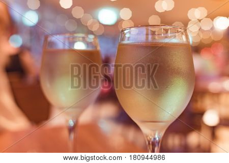 Party Blurred Background With Two Glasses Of White Wine