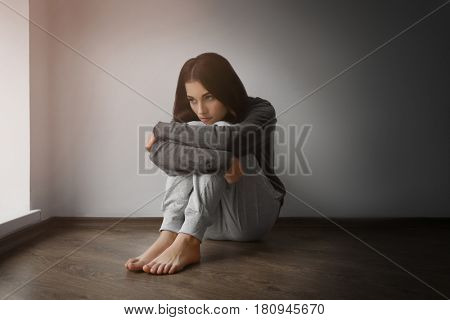 Depressed young woman sitting on floor in empty room