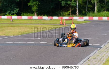 OLDENZAAL NETHERLANDS - JUNE 7 2016: Boy karting on an empty karting track