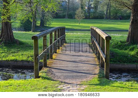 Old wooden bridge curving over a small stream in a park,