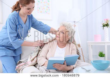 Nurse caring for elderly woman in light room