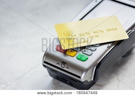 purchase payment with credit card through terminal on stone table background