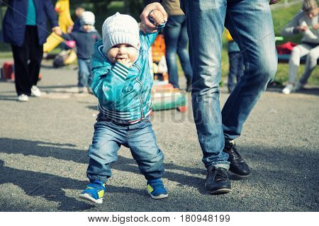 Father and son walking in the park on summer day. Little child holding hand of a man