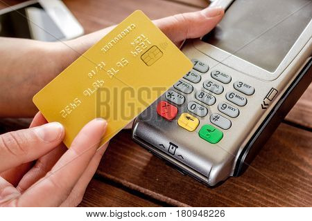 Online payment concept with credit card and terminal for business lunch on wooden table background