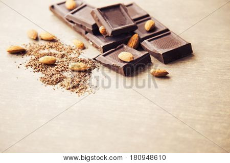 Pieces of dark chocolate with almonds and a grated chocolate crumb