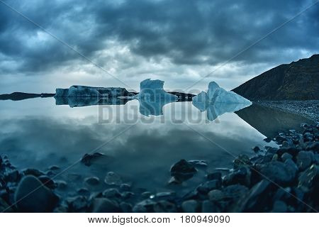 Glacial lagoon in Iceland in the fall. Cloudy foggy weather, mountains on the horizon. The glacial lake reflects the sky, glacier and mountains