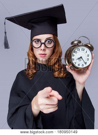 Photo Of Beautiful Young Alumnus With Alarm Clock On The Wonderful Grey Studio Background