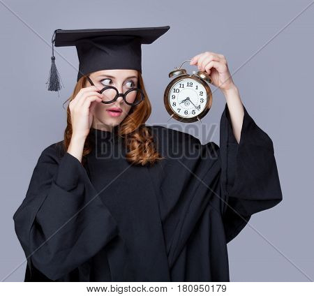 Photo Of Beautiful Young Alumnus With Alarm Clock On The Wonderful Grey Studio Background