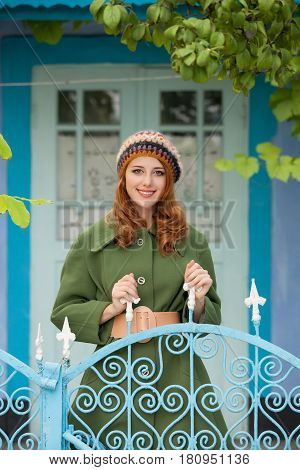 photo of beautiful young woman standing near gate on the wonderful building background