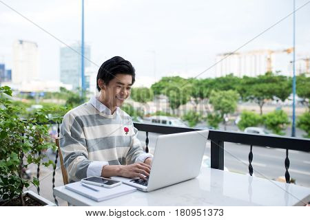 Asian Young Business Man Working With Laptop At The City Cafe.