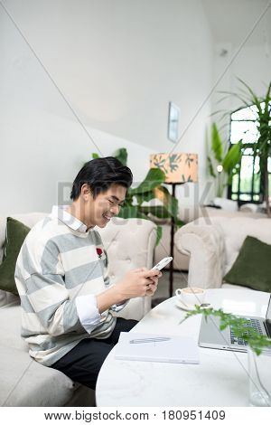 Asian Male Student Texting By Phone While Sitting At The Cafe Shop