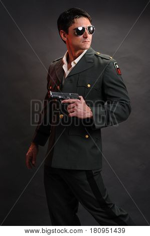The stud military man is holding a pistol.