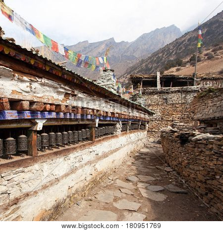 Buddhist prayer many wall with prayer wheels in nepalese village round Annapurna circuit trekking trail Nepal