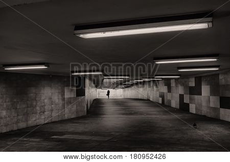 Black and white image of an underground passage. In the background, the silhouette of a woman is visible.