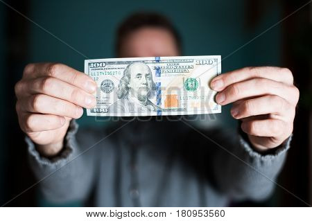 One hundred dollar bill in the men's hand.
