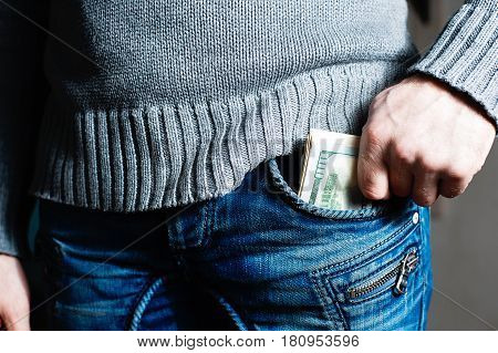 human hand is putting money in the jeans pocket