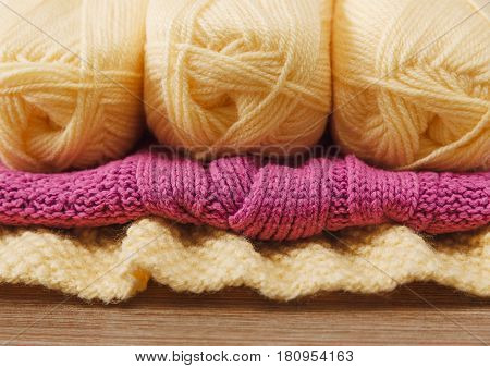 Yellow and Pink Knitted Items.Yellow Balloon of Yarn on the Wooden Table.Hand Made;Fancywork.Selective Focus