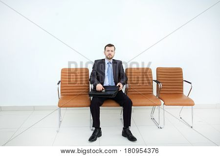 Businessman waiting for business meeting in modern office.