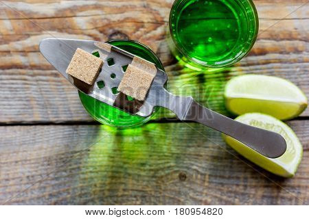 absinthe shots with fresh green lime slices and sugar cubes on wooden bar table background top view