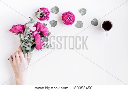 Modern spring design with bright pink flowers in hand on white desk background top view moke up