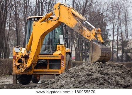 A large yellow excavator stands in the middle of the street near the dug hole.