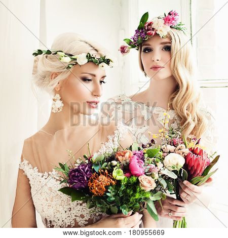 Two Beautiful Blonde Women Fiancee. Fashion Model with Flower Arrangement Flower Wreath Wedding Hairstyle and Makeup