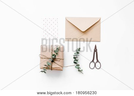 homemade gift wraped in box composition for birthday celebration on white desk background top view mock-up
