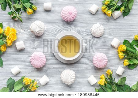 woman breakfast with yellow roses and marsh-mallow on light wooden table background top view pattern