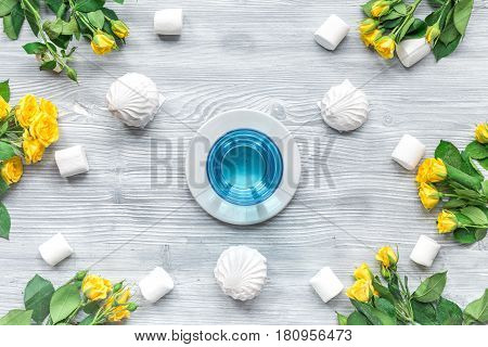 woman table trendy design with yellow flowers and marsh-mallow in soft light on wooden table background top view pattern