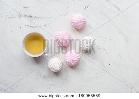 woman office desk with tea and marsh-mallow in spring desing on light wooden background top view mockup