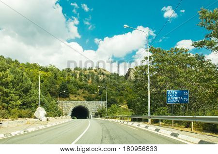 Road And Tunnel In Mountains Along Sea Crimea In Clear Sun, Cloudy Day