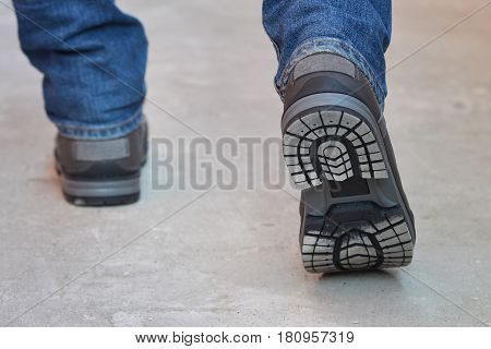 Young fashion man's legs in jeans and boots walking away, sole view.