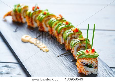 Dragon shape Sushi rice roll with nori prawn avocado sesame and teriyaki