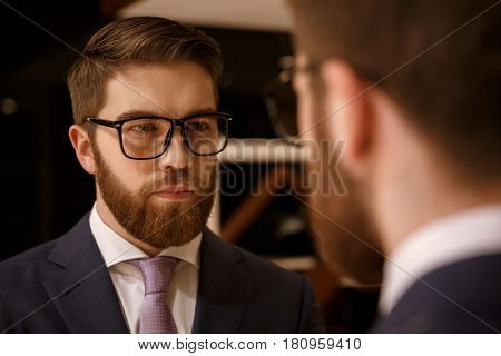 Photo of concentrated young bearded businessman standing indoors. Looking at mirror.
