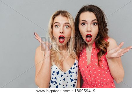 Image of shocked young two ladies friends with bright makeup lips standing over grey wall and posing. Looking at camera.