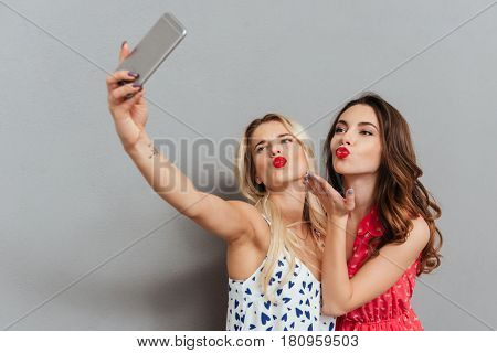 Photo of two pretty happy young women posing over grey background. Looking aside and make selfie.